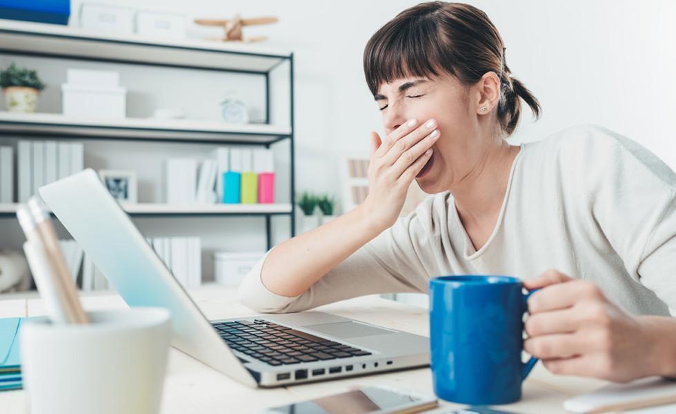 Nainen haukottelee työpöydän ääressä.