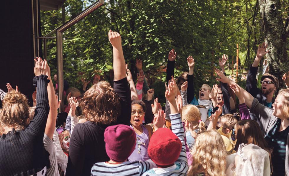 Iso joukko nuoria ja lapsia ulkona viittaamassa kädellään.