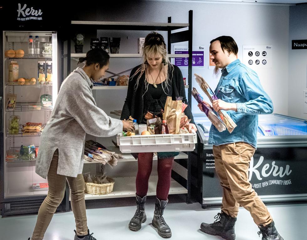 Kolme henkilöä kerää elintarvikkeita laatikkoon.
