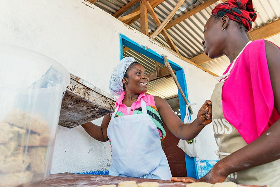 Kaksi naista leipoo sämpylöitä.