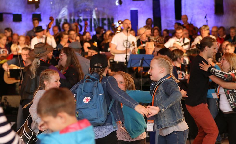 Suuri määrä eri-ikäisiä tanssijoita- ja muusikoita.