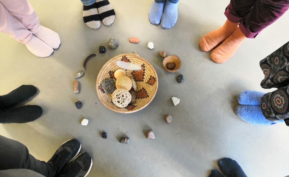 Ihmisten jalat ringissä luonnonmateriaaleista rakennetun taideinstallaation ympärillä.