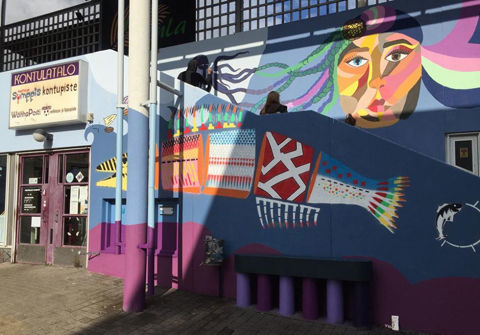 Ihmisiä maalaamassa värikästä muraalia talon seinään.