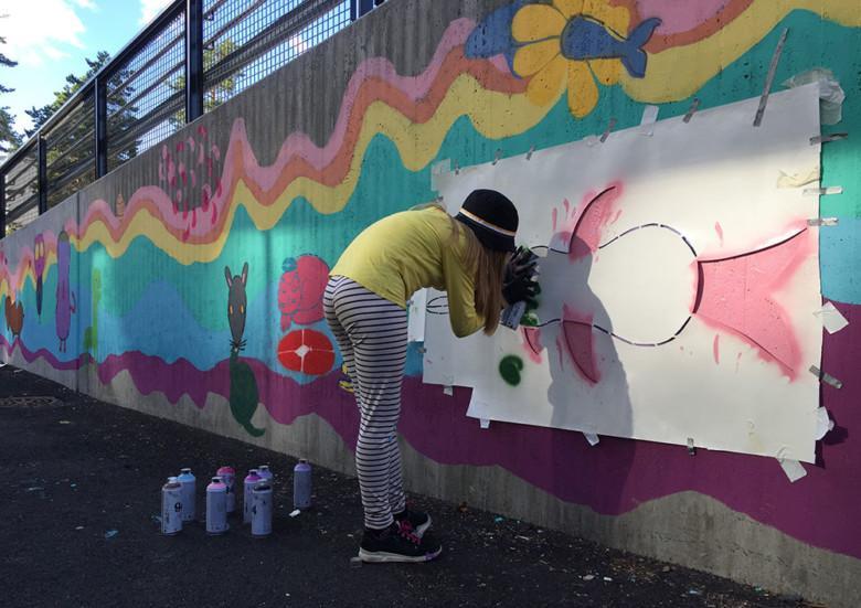 Lapsi maalaa värikästä kuvaa ulkoseinään.