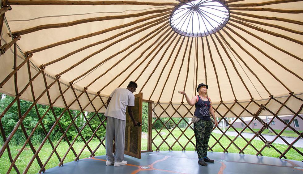 Etniseltä taustaltaan erilaiset mies ja nainen nurmikolle pystetyssä jurtassa.