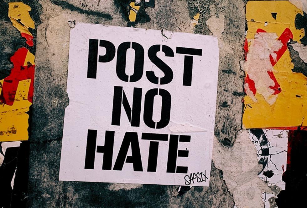 """Seinään liimattu juliste, jossa on teksti """"Post no hate""""."""