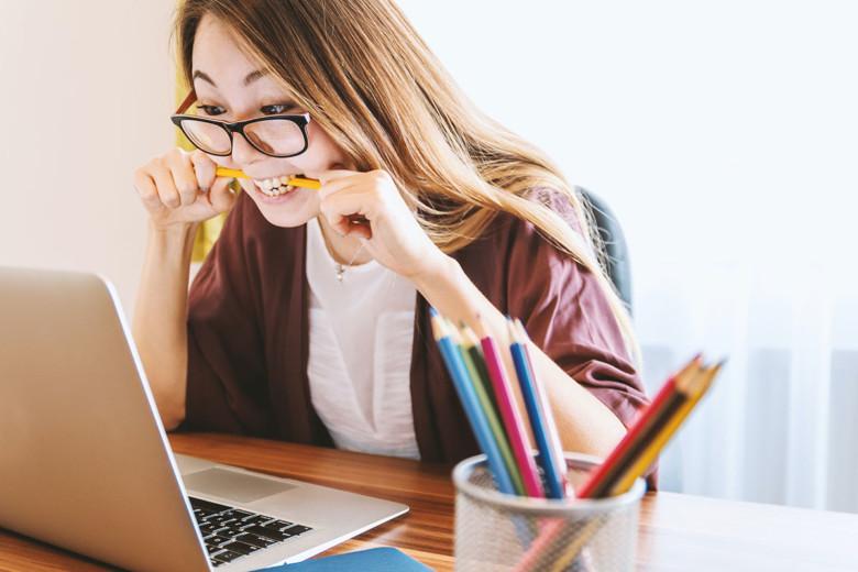 Nainen puree jännityneenä kynää kannettavan tietokoneen ääressä.