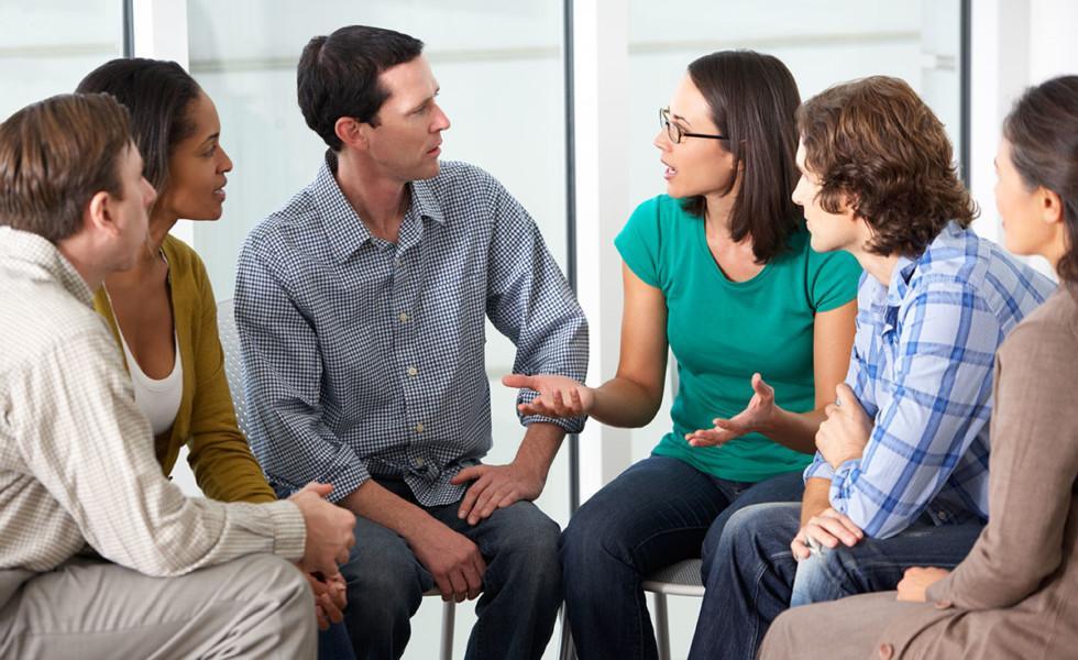 Ryhmä ihmisiä kuuntelee kiinnostuneena naista.