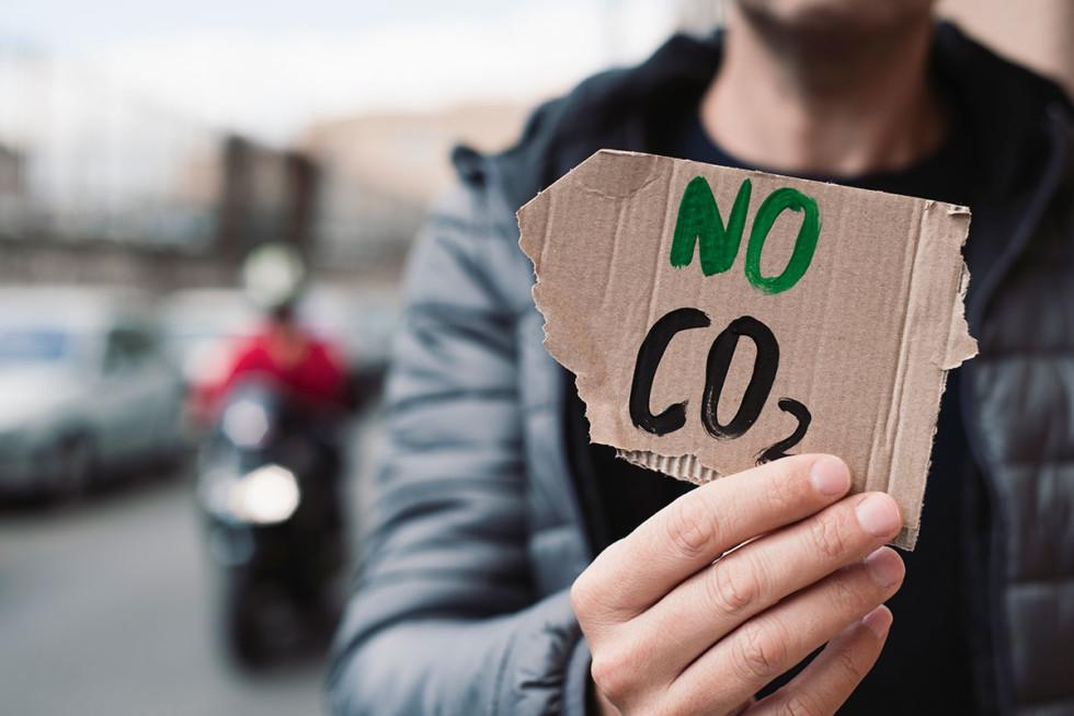"""Mies näyttää kylttiä, jossa lukee """"No CO2""""."""
