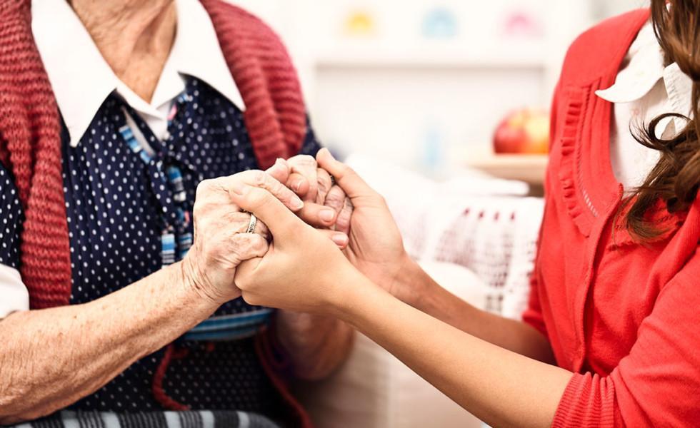 Nuorempi ja vanhempi nainen ovat liittäneet kätensä yhteen.