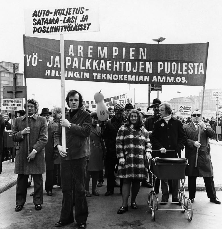 Ihmiset kantavat kylttejä vappumarssilla vuonna 1972.
