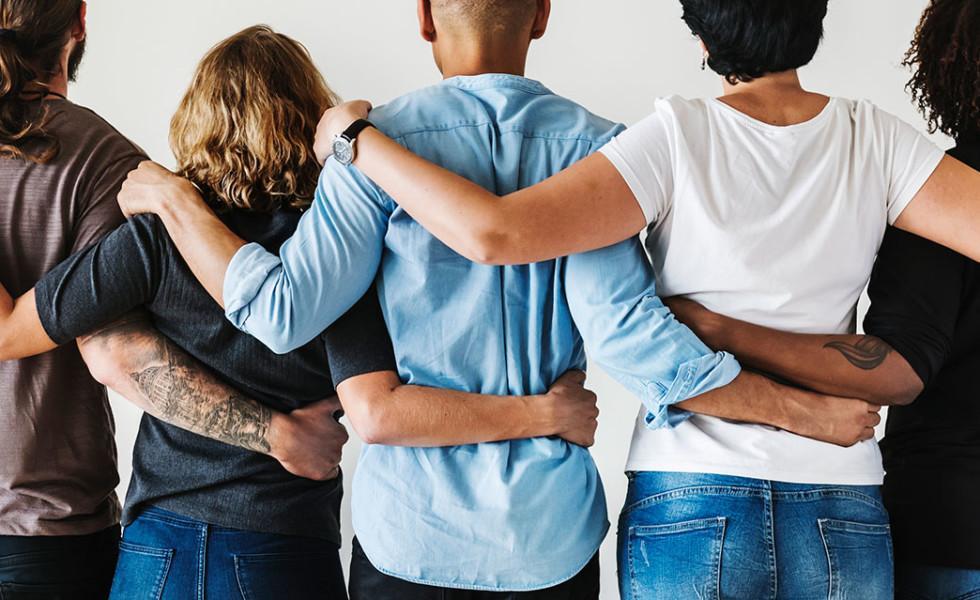Joukko ihmisiä kuvattuna takaa kädet toistensa olkapäillä ja vyötäröllä.