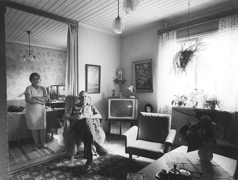 A couple in their home in 1970. On the corner of the living room there is a television.