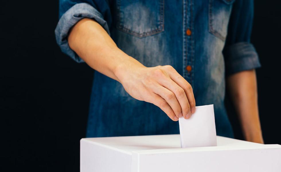 Nuori henkilö laittaa äänestyslipukkeen uurnaan.