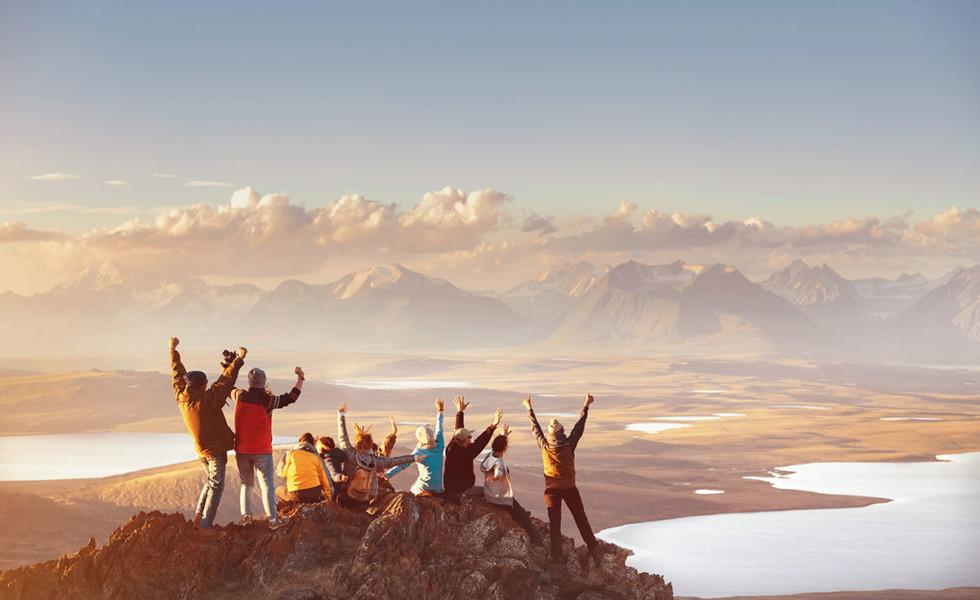 Joukko ihmisiä riemuitsee vuoren huipulla.