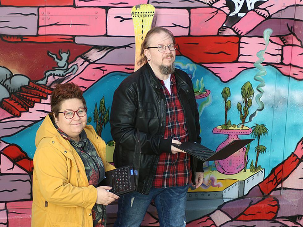 Piia Niilola ja Janne Haikka läppäreineen värikkään seinämaalauksen edessä.