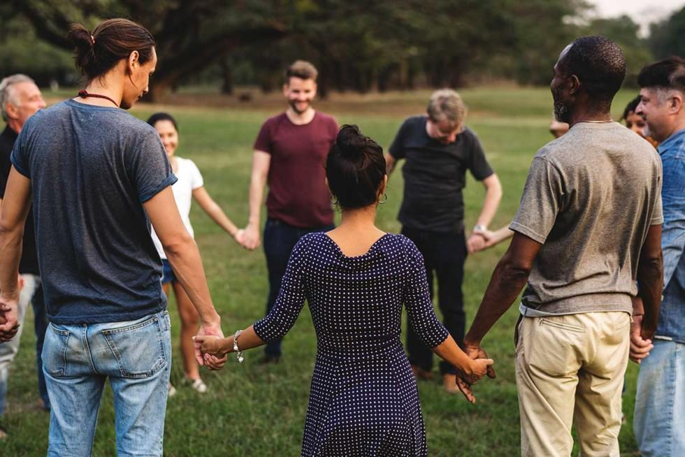 Moninainen ryhmä ihmisiä seisoo ringissä ja pitää toisiaan kädestä.t
