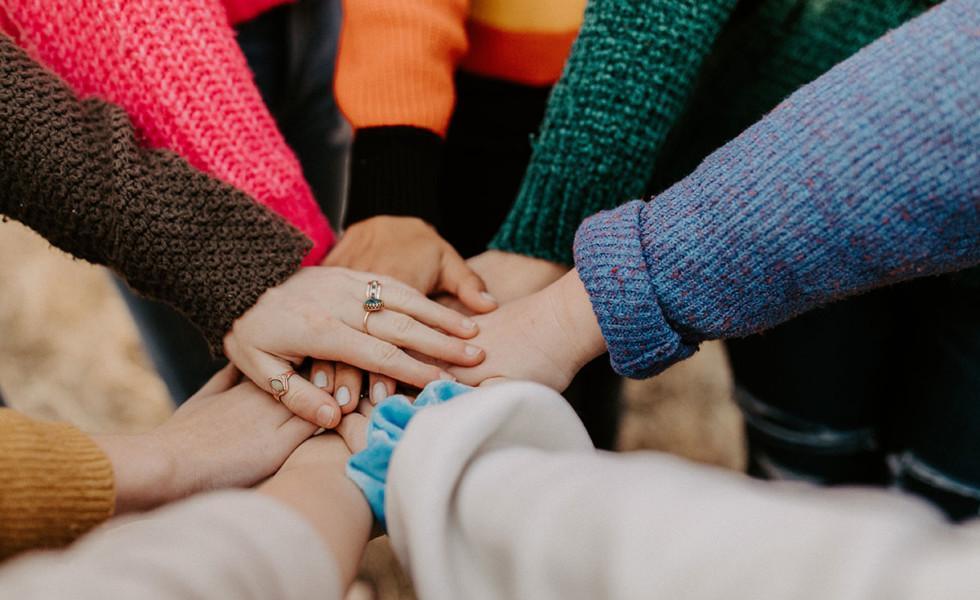 Joukko ihmisiä on liittänyt kädet yhteen.