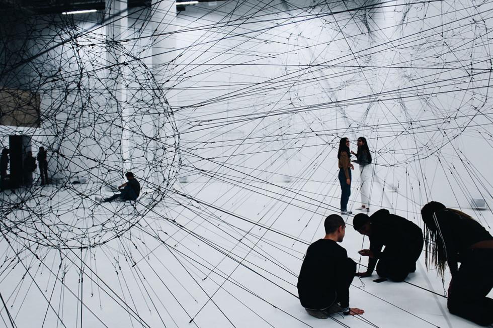 Joukko ihmisiä tutkii verkkomaista taideteosta.